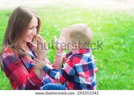 Happy Mother and Her Son in Similar Shirts and Jeans Playing in Hands. They are Sitting on Green Grass in the Summer Park