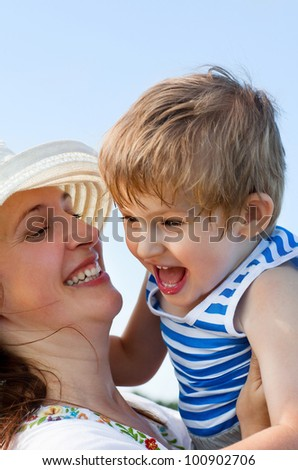 happy mother and her son on blue sky background