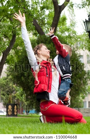 Happy mother and her son playing at the park - family concepts - stock photo