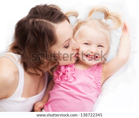 happy mother and her two year old daughter in bed at home, top view