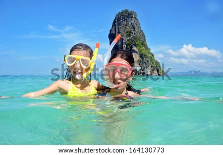 Happy mother and kid snorkeling in tropical sea, family beach vacation