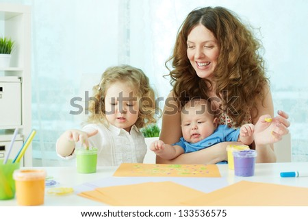 Happy mother and kids doing finger-painting