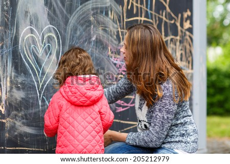 Happy mother and little beautiful daughter drawing with chalk in park, outdoors