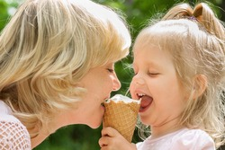 Happy mother and little daughter eating ice cream in summer day