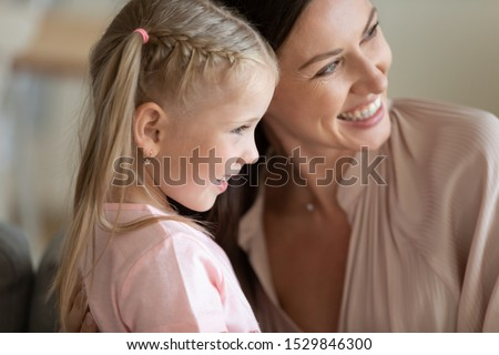 Happy mother and little daughter hugging, posing for family photo profile close up, smiling beautiful young woman and adorable preschool child embracing, having fun together, making picture