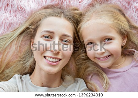 Happy mother and little daughter with blonde hair lying on pink fur and making selfie. Two beautiful people, family concept