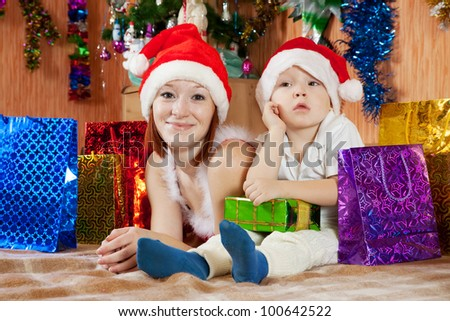Happy mother and little son with Christmas gifts at  home