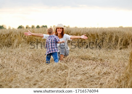 Happy mother and son are running through a wheat field in summer ストックフォト ©