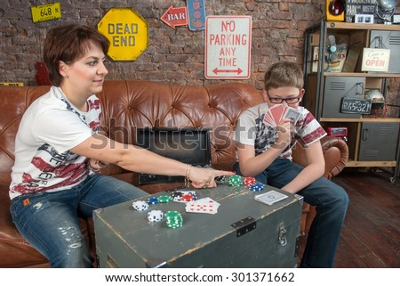 Happy mother and son playing in an entertaining game at home - leisure, games and lifestyle concept