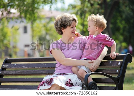 Happy mother and son sitting on bench in park