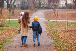 Happy mother and sons going to school and to kindergarten. Mother with two sons on walk in autumn. Back to school. Happy family in autumn park