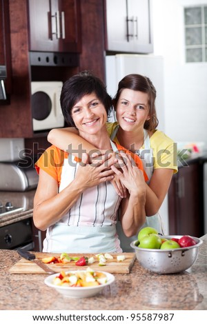 happy mother and teen daughter in kitchen