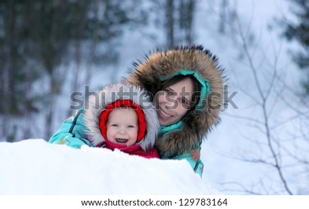 Happy mother and toddler daughter having fun in a winter park
