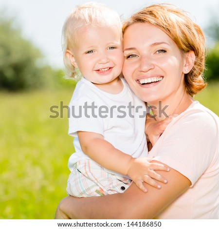 Happy mother and toddler son in the spring meadow outdoor portrait