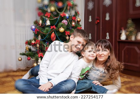 Happy mother and two her children playing near an decorated fir-tree for Christmas