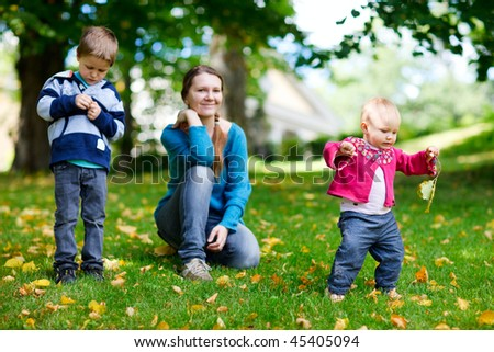 Happy mother and two kids spending time outdoors at sunny autumn day