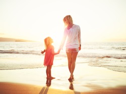 Happy mother and young daughter on the beach at sunset