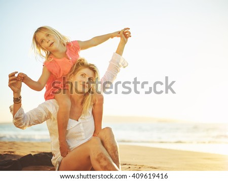 Photo of Happy mother and young daughter on the beach at sunset