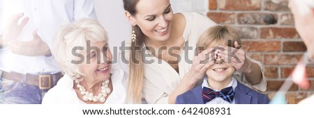 Happy mother covering her little sons eyes