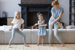 Happy mother dancing, having fun with two daughter in modern living room. Family playing funny game. Young mom and adorable cute girls moving to favorite music, enjoying weekend at home.