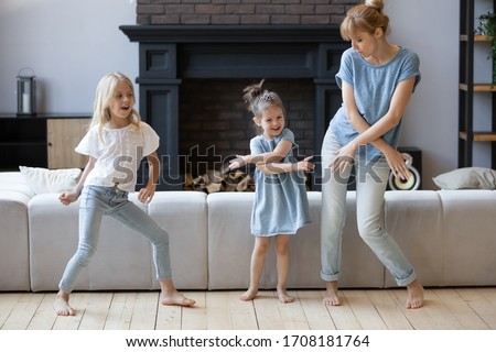 Happy mother dancing, having fun with two daughter in modern living room. Family playing funny game. Young mom and adorable cute girls moving to favorite music, enjoying weekend at home. Stockfoto ©
