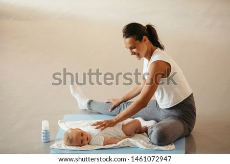 Happy mother doing relaxation exercises on the floor while having fun with her baby in health club.