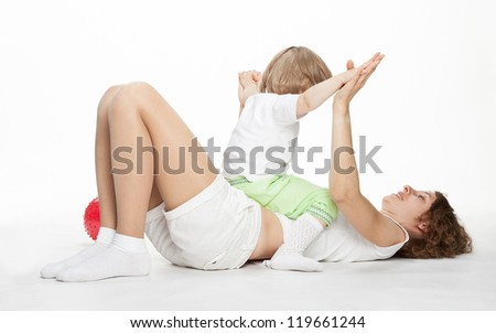 Happy mother doing sport exercises with little daughter on white background