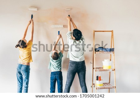 Happy mother, douther and son painting wall with roller. Mom teachs her children painting with roller at home. Foto stock ©
