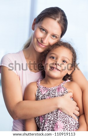 Happy mother embracing her daughter and looking at camera - stock photo