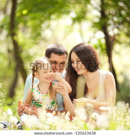 Happy mother, father and daughter playing in the park - stock photo