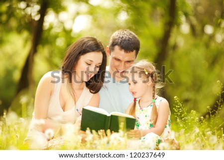 Happy mother, father and daughter read a book in the park