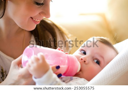 happy mother feeds the baby bottle