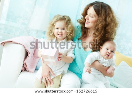 Happy mother giving her children a hug, her daughter holding a gift-box