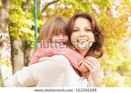 Happy mother giving piggyback ride. Shallow focus.