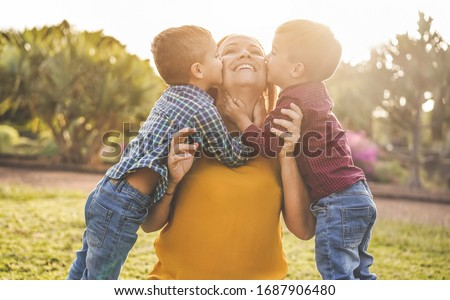 Happy mother having fun with her two sons playing outdoor - Love and family concept - Focus on mother face