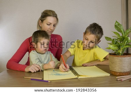 Happy mother helping her sons with homework