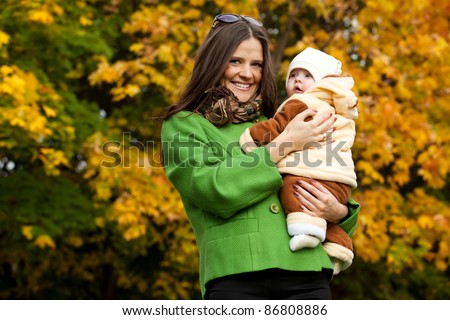 happy mother holding baby in park. a bright autumn day.