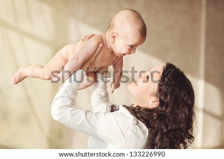 happy mother holding her baby and playing with him indoors