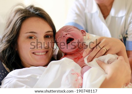 Happy mother holding her baby, seconds after she gave a birth, natural child birth