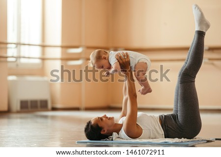 Happy mother holding her baby while exercising on the floor in health club.