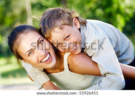 Happy mother holding her cute son and both laughing