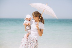 Happy mother holding her little baby girl on the beach in Dubai. In one hand she is holding a white parasol