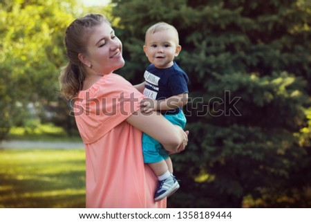 Happy mother holds a small child in her arms in the park. Little cute baby in his mother's arms. Portrait of mom with her son in nature. #1358189444