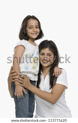 Happy mother hugging her daughter and smiling