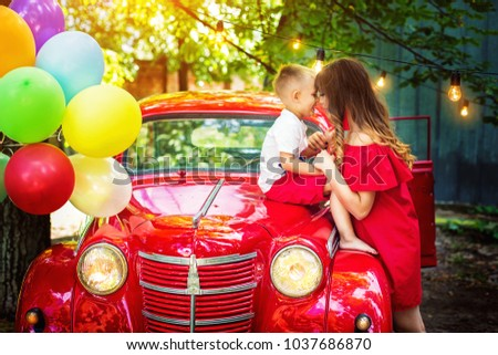 Happy mother hugging her son. Child is sitting on hood of red retro car. Bright balloons tied to car. Birthday of child