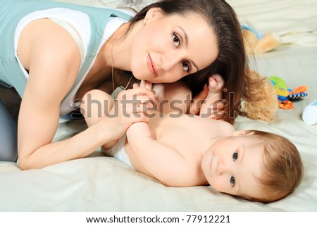 Happy mother is playing with her baby.