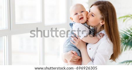 Happy mother kisses her baby toddler