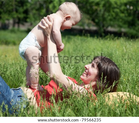 Happy mother lay with new born baby on grass in park