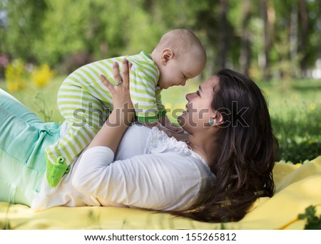 Happy mother lay with newborn baby on grass in park