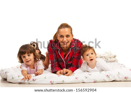 Happy mother lying in bed with her little kids against white background